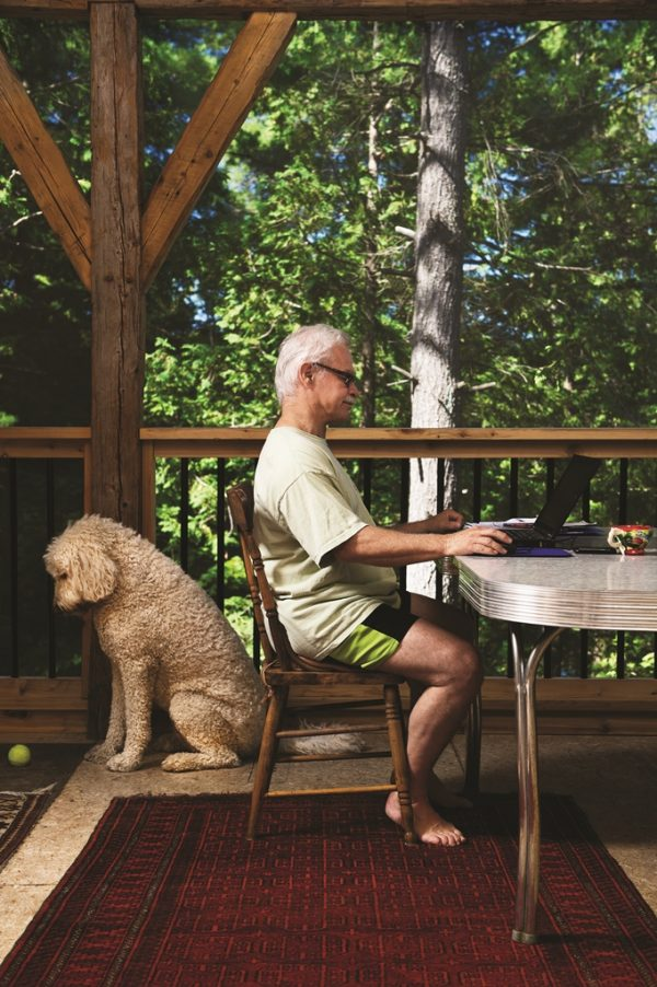 Dog facing right, Ted Jackson facing left on computer at their cottage on the porch. Trees in background with wooden beams from family farm used to construct the porch.